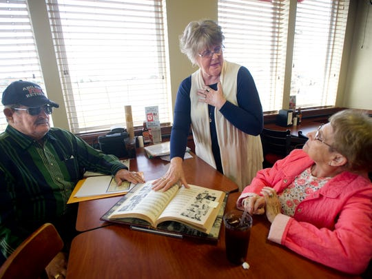 Sharon Densman, center, shows a photo of her half-brother to James and Pat Smith. Smith died recently, severing a connection to Sharon's half-brother, who died during World War II.