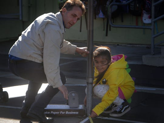John Puglisi, the Rio School District superintendent, works with Stephanie Sanchez, a fifth grader at Rio Plaza School, on measuring the sun point in an exploration space and time assignment.