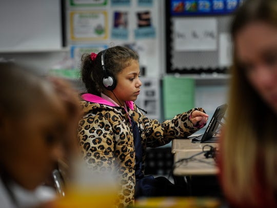 Jessica Ibrahim, 7, reads off a computer screen in her second grade sheltered English language class at Una Elementary School in Nashville on Dec. 16, 2016.