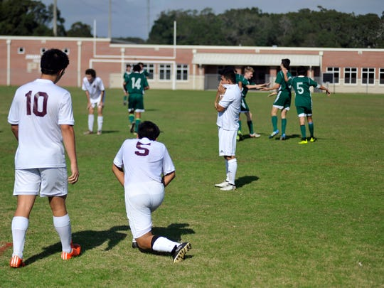 Players react after John Carlson's pass deflected off a Pensacola High defender and into the goal for Catholic's late winning goal on Dec. 17, 2016.