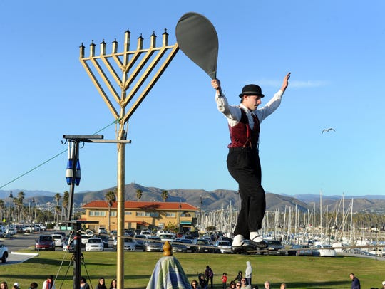 Tightrope walker and acrobat Chris Grabher keeps the audience's attention during a Hanukkah festival a few years ago in Ventura.