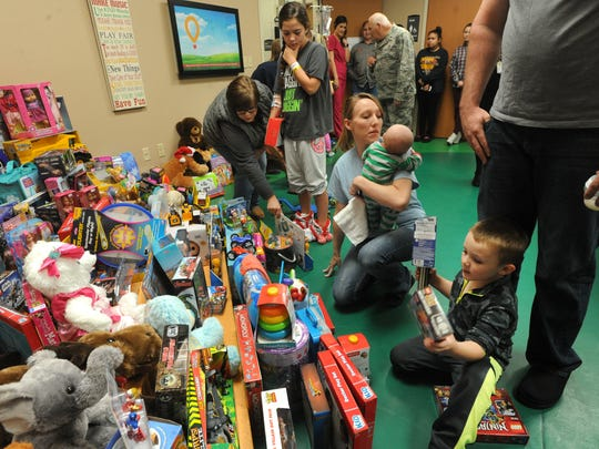 Emily Richburg, center, and her boys Carter, 2 months, and Kyler, 4, get some of the toys donated by the Texas State Guard to children hospitalized at Hendrick Medical Center on Tuesday, Dec. 20, 2016.