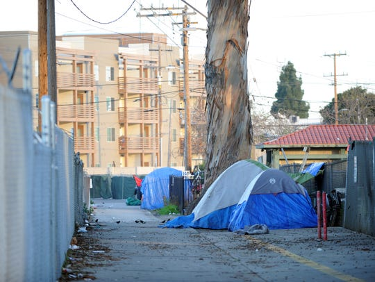 FILE -- New affordable housing looms behind tents of the homeless in an alley off Market Way in Salinas.