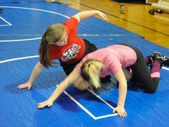 Kallie Grove, left, practices wrestling with Natalie