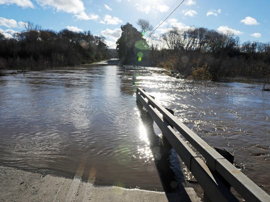 Davis Road disappears under the Salinas River on Thursday due to heavy seasonal rains. The road is closed to through traffic.
