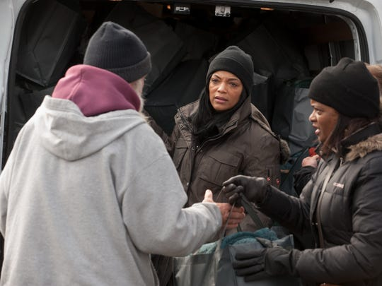 Yvette Anderson (center) hands out clothes and food to the needy in Asbury Park.