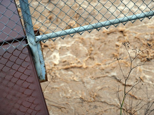 Framed by a footbridge along Russell Rd. in north Salinas, muddy water from heavy rains courses through Santa Rita Creek.