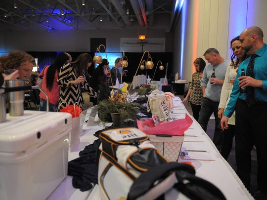 People bid at the silent auction at The Compass Center's