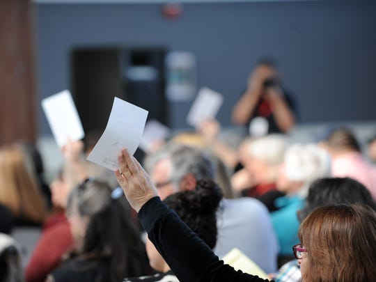 Members of the audience wave questions for panelists at an immigration town hall on Sunday at Hartnell College in Salinas.