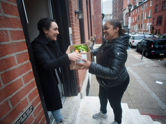 Hungry Harvest staff member Larayna Dunson delivers vegetables to Emily Coch at her home on Spruce Street in Philadelphia.