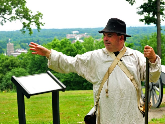 Eric Olsen, Park Ranger/Historian, dressed as a militia or Continental soldier, near the overlook toward New York City. At right is a replica of a British 6-pound bronze canon, similar to those captured at Princeton and brought to Morristown. Fort Nonsense reopens officially on July 4 after suffering damage from superstorm Sandy due to its high elevation. The property is renovated and has new picnic tables and signs. Tom Ross, superintendent of Morristown National Historical Park, Eric Olsen, Park Ranger/Historian, and Eileen Cameron, President Washington Association of New Jersey attend.  Morristown, NJ. Thursday, June 19, 2014. Special to the NJ Press Media/Karen Mancinelli/Daily Record MOR 0619 fort nonsense