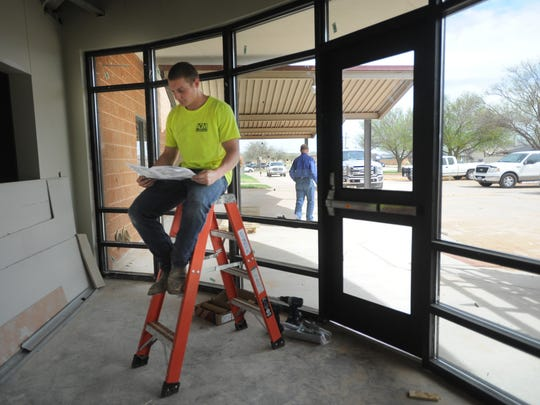 Cullen Bland from Abilene Glass and Mirror works to finish installing windows at the front of the former Jane Long Elementary School, which will reopen as an early childhood center.
