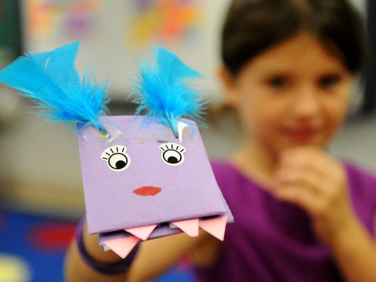 Bridgette Rosser shows off her purple puppet she made during the YMCA Summer Learning Loss Prevention program at Evans School in 2014.