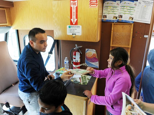 Inside the Salinas Public Library's Bookmobile, librarian Luis Alejandre checks out several volumes for Oasis Charter Public School student Rosario Villafa–ña.