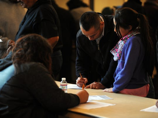 Attendees at an immigration forum held on Monday fill out surveys for the city of Salinas.