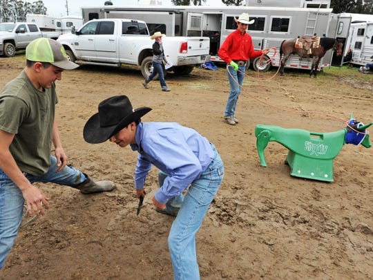 From left, Chase Sievers and Tucker Bourdet play stretch, while a fellow competitor practices roping at the California High School Rodeo competition on Sunday at the Salinas Sports Complex.