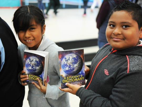 Jasmine Vargas, 9, and Gaspar Pantoja, 8, hold up their new dictionaries at the Alisal Community School.