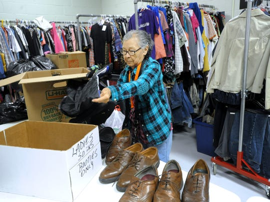 Naomi Castillo unpacks shoes and clothes at the new location of the Christian Service Center, which re-opened today at 3185 N 10th Street.