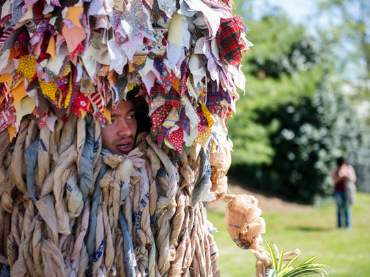 Dominic Brennan educates scavenger hunt participants about compost while dressed as a tree, at EarthFest in World's Fair Park in downtown Knoxville on Saturday, April 16, 2016.