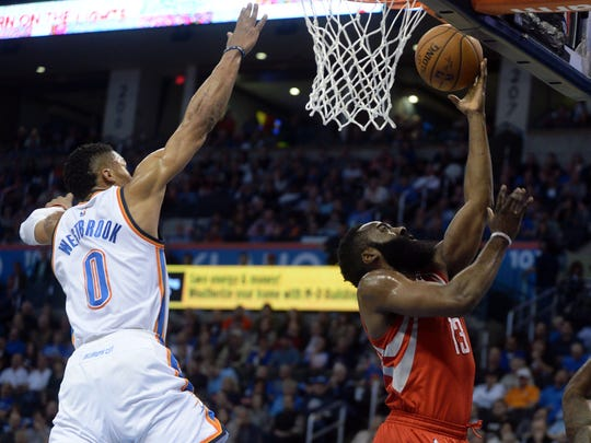 Russell Westbrook blocks a shot attempt by James Harden.