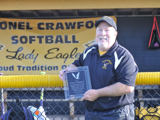 "Chuck Huggins holds his 600th win plaque athletic director David Sheldon surprised him with ahead of a game against Bucyrus. Huggins said he can always count on Sheldon to send a ""go get 'em Huggs"" or congratulatory text each game."