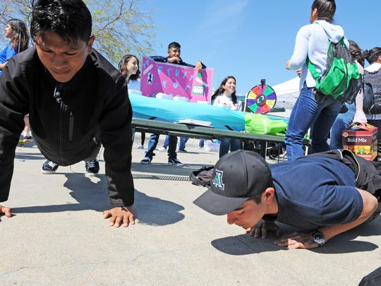 Jorge Gabriel, left, and Isaac Calvillo Bernal show how to do pushups properly at Alisal High School's first Community Health and Wellness Fair on Thursday.