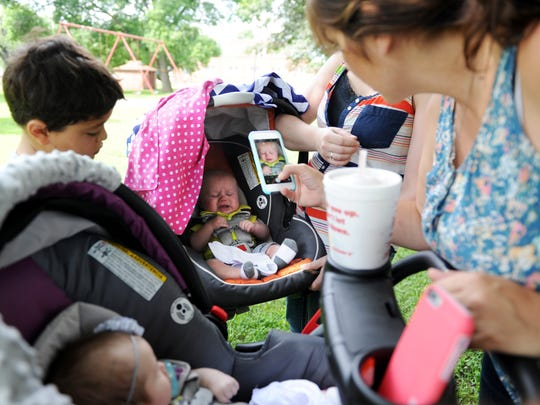 ERIN MCCRACKEN / COURIER & PRESS Tara Pearce (right) snaps a quick cellphone picture of four month-old, Blaine McCarter, as his mother Sara McCarter gets the twins ready to head home after a play date with Pearce at Gregg Park Vincennes, Indiana on Thurs. July 16, 2015. Pearce was a surrogate for McCarter's twins and their families have since formed a close relationship.