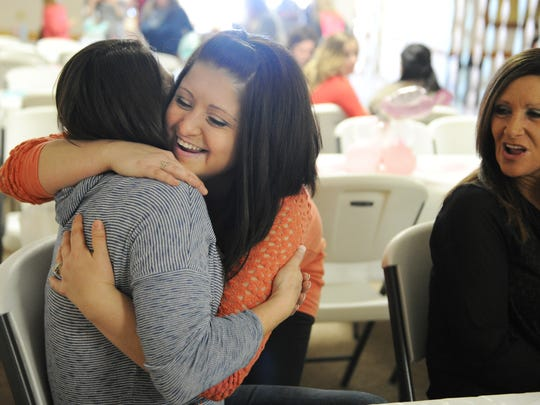 ERIN McCRACKEN / COURIER & PRESSSara McCarter hugs her coworker and friend Colleen Russell and thanks her from coming to her baby shower at St.Vincent Catholic Church in Vincennes, Ind., on Feb. 7, 2015. McCarter feels blessed to have such an amazing and supportive group of friends she works with who have helped support her through the surrogacy process. It was her coworker Chris Pearce who approached his wife about helping Sara and her husband Zach become parents through surrogacy.
