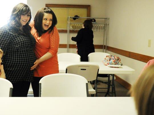 ERIN McCRACKEN / COURIER & PRESSSara McCarter (left center) introduces her surrogate, Tara Pearce, and her babies to her family members at a baby shower at St.Vincent Catholic Church in Vincennes, Ind., on Feb. 7, 2015. Pearce, who has five children of her own, offered to be McCarter's surrogate so that she can become a mother, something she desperately has wanted for a long time but is unable to carry her children.