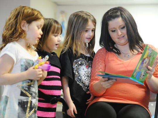ERIN McCRACKEN / COURIER & PRESSSara McCarter thumbs through a baby book as Caroline Pearce, McCarter's surrogate's daughter, and her nieces, Gianna Mundo and Cori Mundo  look over her shoulder as she opens gifts at her baby shower at St.Vincent Catholic Church in Vincennes, Ind., on Feb. 7, 2015. Friends and family gathered to celebrate Sara and her husband Zach's babies, who will be born through a surrogate in early April. Though the couple is not experiencing a regular pregnancy they are going through the traditional preparations of preparing their home for their twins, Blaine and Mila.