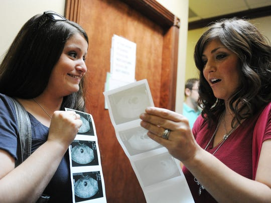 Sara McCarter  and Tara Pearce look at ultra sound pictures of Sara and her husband Zach's for whom Pearce is a surrogate following viability ultrasound which occurred at six weeks and six days of the pregnancy at the Advanced Reproductive Institute in Evansville on August. 29, 2014.  Pearce 's husband Chris is Sara's coworker, when he heard that Sara was looking for a surrogate he and his wife volunteered to help make Sara and her husband Zach's dream of becoming parents a reality.