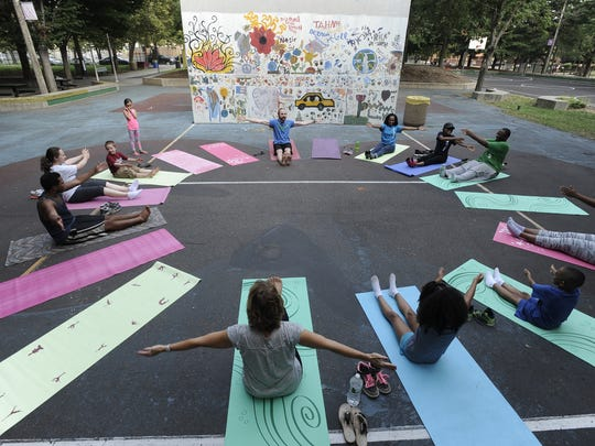 Yoga instructor Chris McCooey leads a 2014 yoga class at North Camden Community Park in Camden, as part of Connect the Lots. Community Park in Camden in 2014 as part of Connect the Lots.
