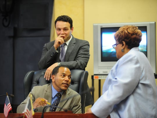 Councilman Julio Tavarez, sitting, with Councilman Andre Sayegh behind him, talking to City Clerk Jane Williams-Warren in 2013.