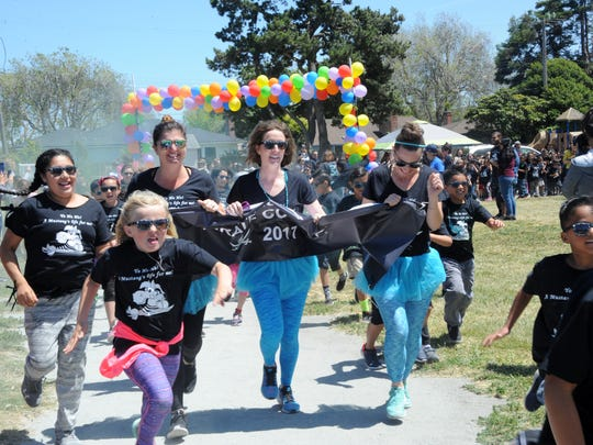Adults kick off the first wave of kids at the Mission Park Elementary School's Pirate Color Run on Wednesday in Salinas.