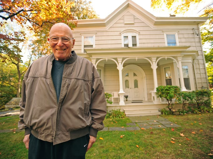 Charles Kaufman poses by his 150-year-old house he