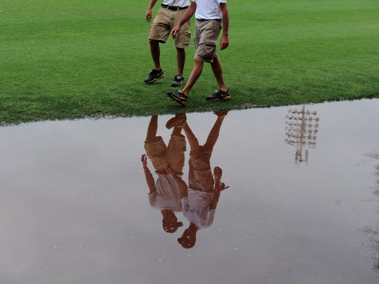 Evansville Otter's ground crew workers, Grady Adler ( left) and Jon Pfettscher (right) walk to go tend to a rain soaked field after the Otter's game against the Washington Wild things  was canceled due to rain on Sunday,  August 17, 2014. Field drainage is on the wish list of Otters owner Bill Bussing.