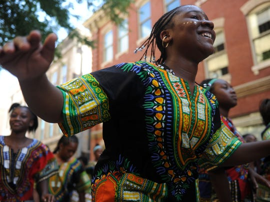 Janna Ellis, 14, dances down Market St. into Market Square during the Kuumba parade, on Friday, June 24, 2016. This is the 27th year of the Kuumba Festival, which is one of the largest African American cultural arts festivals in East Tennessee. (CAITIE MCMEKIN / NEWS SENTINEL)