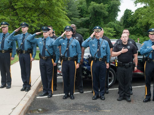 New Jersey State Troopers salute the flag during a