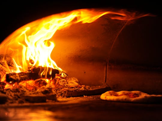 Flames crawl up the sides of the pizza oven as a pizza cooks on Friday, June 9, 2017, at Vagabond Pizza.