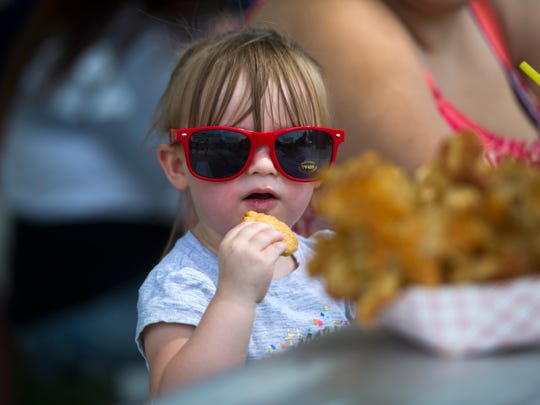 Alifair Childs, 2, of Sevierville, enjoys a potato chip at the Secret City Festival in Oak Ridge on Saturday, June 10, 2017. The Secret City Festival celebrates the arts, culture, and history of Oak Ridge.