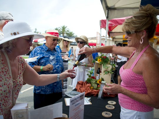Pam Chase (left) holds out her glass while Debby Giovinazzo (right) of Sunland Vintage Winery gives her a sample of wine during a past event.