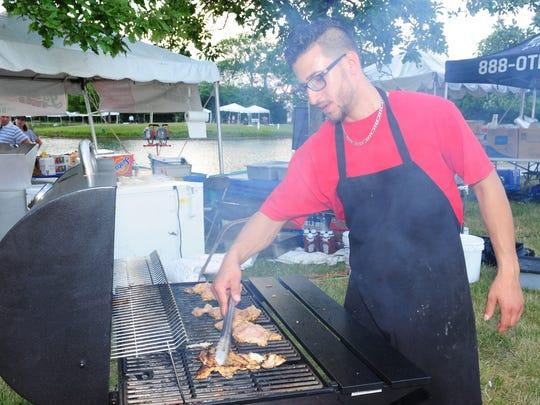 Canton restaurant, La Shisho Palace employee Steve Varha prepares grilled chicken for delicious Chicken Shawarma sandwiches.