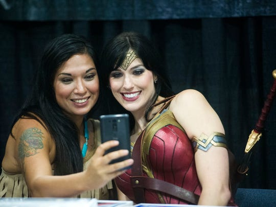 Donna Bender of Knoxville, dressed as Pocahontas and Shannon Prince of Murfreesboro, dressed as Wonder Woman take a selfie together at the Fanboy Expo in the Knoxville Convention Center Saturday, June 24, 2017.