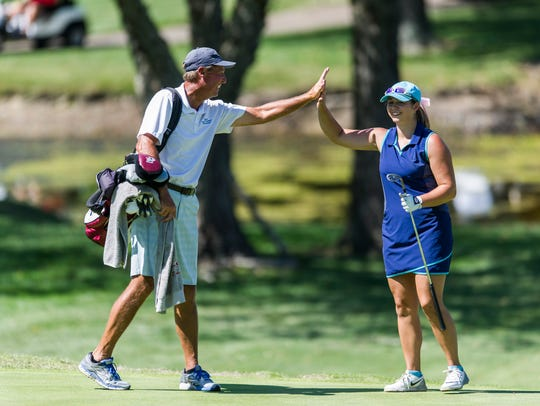 Caddie and golf pro Mike Wolf high fives Emma Kieffer