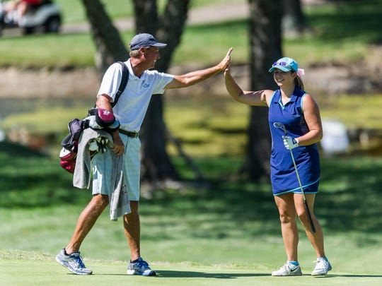 Caddie and golf pro Mike Wolf high fives Emma Kieffer after she eagled the 18th hole and won the Women's City Golf Tournament at Rolling Hills Country Club in Newburgh, Ind., on Tuesday, June 27, 2017.