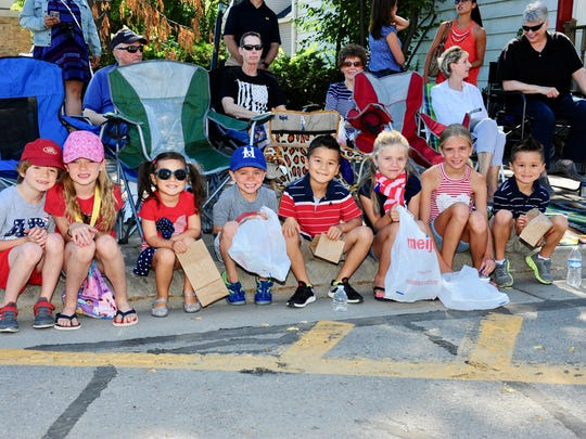 Kids line up along Main Street with smiles as they get ready for the start of this year's Fourth of July Parade.