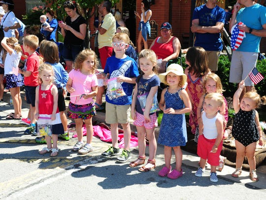 Kids line the streets of downtown Milford during the