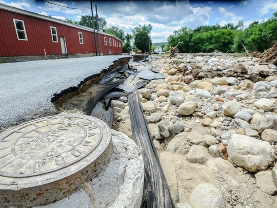 This Monday, July 3, 2017, photo shows  a washed away portion of Newton Road in Brandon, Vt., after heavy rains on July 1. According Daryl Burlett, Director of Brandon Public Works, rocks clogged the Neshobe River up stream, causing it to divert its path across Newton Road.