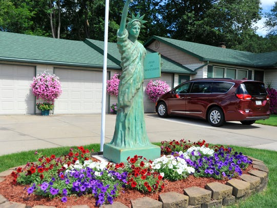 Red, white and purplish-blue flowers surround the base of the Statue of Liberty in Herb and Helen's front yard near the roundabout on Second Avenue in Wisconsin Rapids.