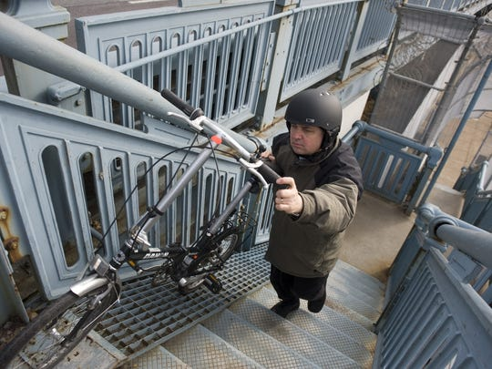 John Boyle, 47, of Edgewater Park, research director of the Bicycle Coalition of Greater Philadelphia, walks his bike up to the steps to the Ben Franklin Bridge walkway from Camden.  A  ramp will replace the stairwell and  make bridge access much easier for riders, pedestrians and the disabled.